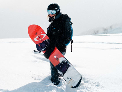 snowboarder carrying snowboard and snowboard bindings
